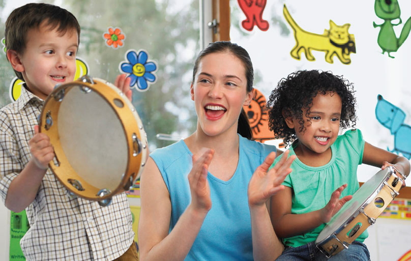A young boy and girl smiling with tambourines and a female instructor clapping